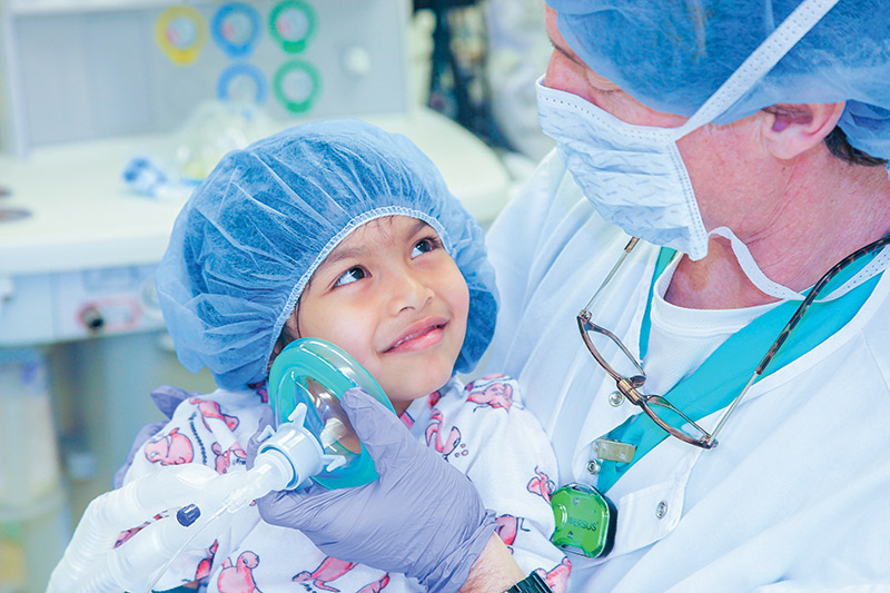 A pediatric patient engages happily with a nurse
