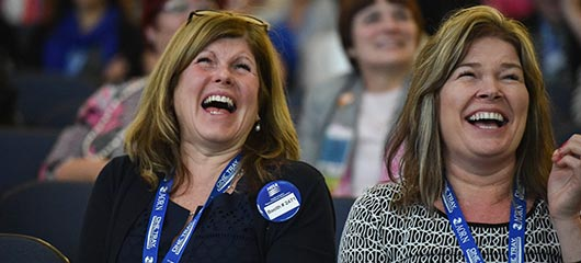Two nurses laughing at Expo general assembly session